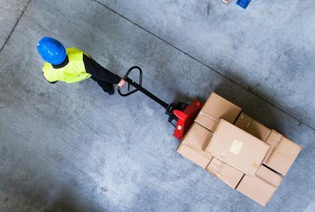 Man pulling pallet truck through warehouse