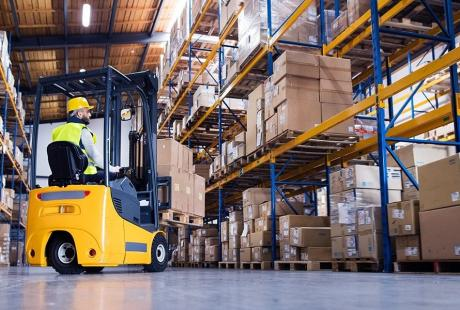 man in forklift in warehouse with racks filled with boxes
